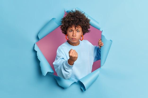화가 불만족 한 젊은 아프리카 계 미국인 여성이 주먹을 보여주고 부정적인 감정을 표현합니다.