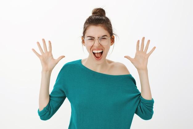 Giovane donna arrabbiata e angosciata con gli occhiali che grida, indignata e incazzata