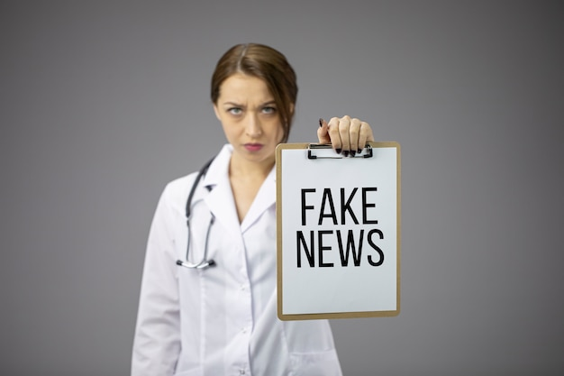 Злой доктор держит буфер обмена с текстом поддельные новости. обман на пандемической трагедии