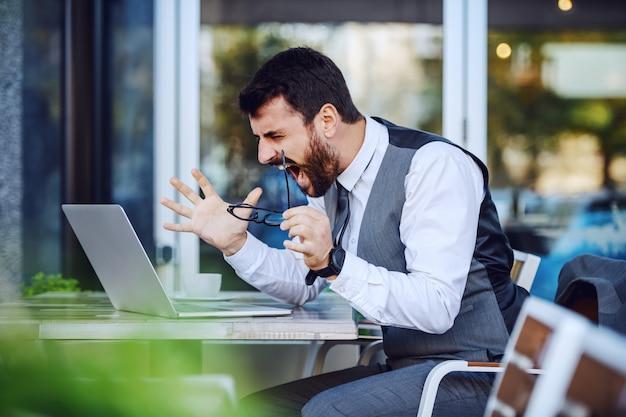 Злой элегантный бизнесмен в костюме смотрит на ноутбук и кричит, сидя в кафе.
