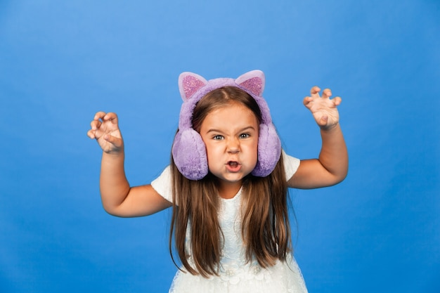 Angry emotional little girl in fur headphones on a blue background.