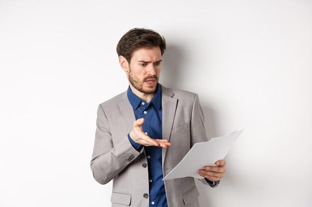 Сердитый работодатель смотрит на плохой документ, жалуется на сделку, указывая на разочарованный документ, стоит в костюме на белом фоне.