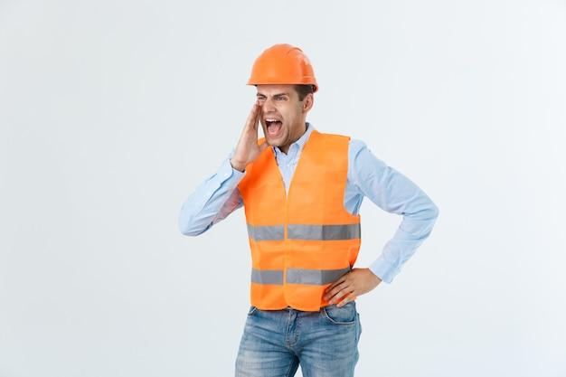 白い背景で隔離、彼の両手を上げている誰かに叫んで怒っている顔の感情を持つ怒っているエンジニア。