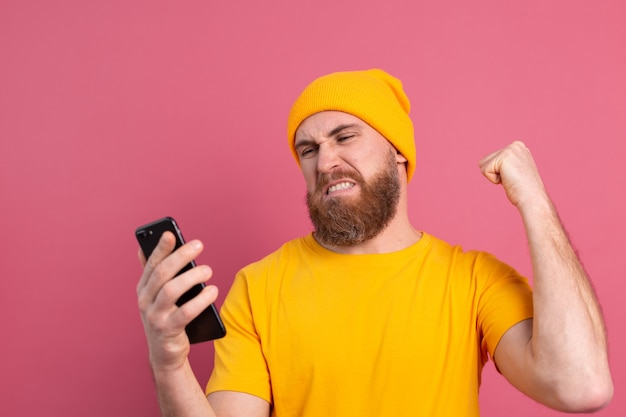 Angry european handsome man angry punching his mobile phone on pink