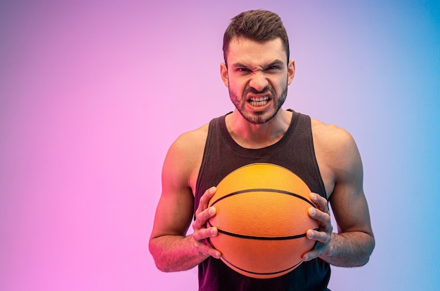 怒っているヨーロッパ人はバスケットボールのボールを手に持っています。若いひげを生やした男はタンクトップを着て、カメラを見ています。青とピンクの背景に分離。スタジオ撮影。コピースペース