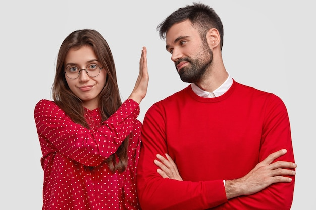 Angry european woman in red blouse makes refusal gesture, keeps palm in front of boyfriends face