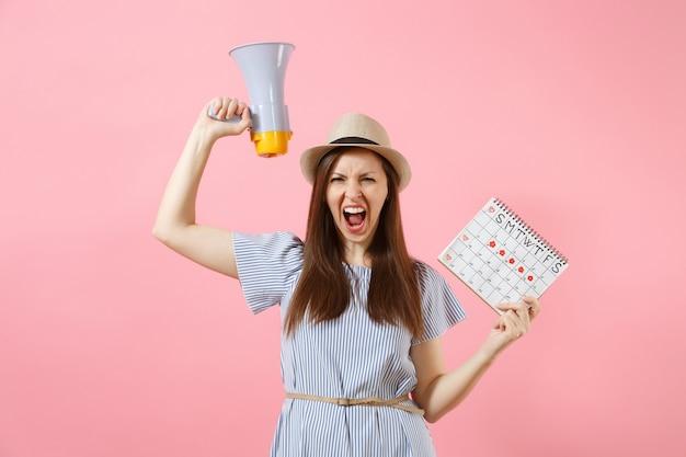 Злой выражение дикая женщина кричала в мегафон, держа календарь периодов для проверки дней менструации, изолированных на розовом фоне. медицинское здравоохранение, настроение пмс, гинекологическая концепция. копировать пространство