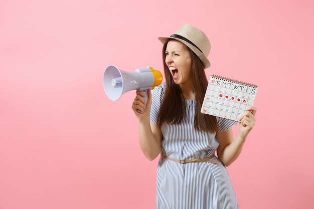 Angry expression wild woman screaming in megaphone, holding periods calendar for checking menstruation days isolated on pink background. medical healthcare, pms mood, gynecological concept. copy space