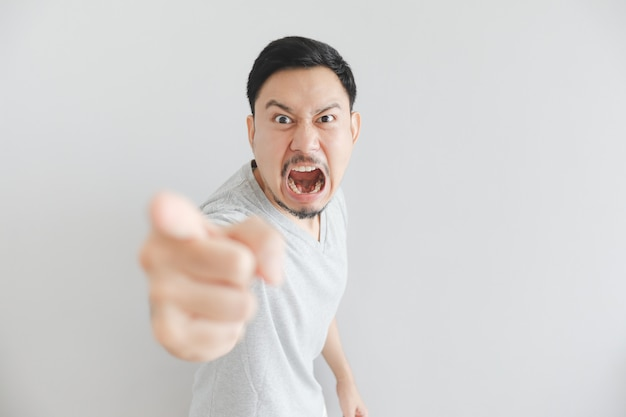 Angry face of man in grey t-shirt with hand point on empty space.