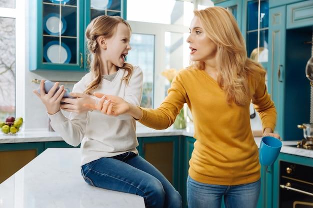 Злая светловолосая худенькая девушка держит телефон и плачет, пока мама его забирает