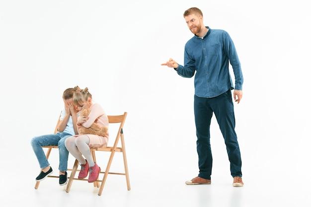 집에서 그의 아들과 딸을 꾸짖는 화가 아버지. 감정적 인 가족의 스튜디오 샷. 인간의 감정, 어린 시절, 문제, 갈등, 가정 생활, 관계 개념