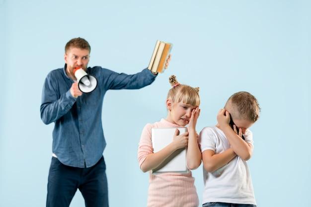 怒った父親が息子と娘を家で叱る。感情的な家族のスタジオショット。人間の感情、子供時代、問題、紛争、家庭生活、人間関係の概念
