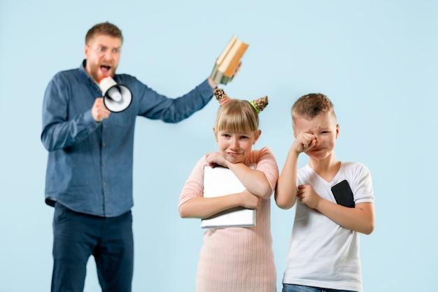 Сердитый отец ругает сына и дочь дома.