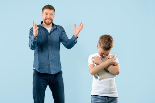 집에서 아들을 꾸짖는 화난 아버지. 감정적인 가족의 스튜디오 샷입니다. 인간의 감정, 어린 시절, 문제, 갈등, 가정 생활, 관계 개념
