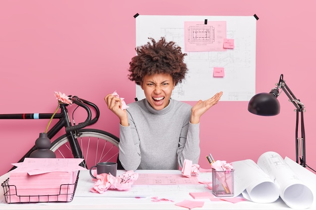 Angry female architect poses at table with papers blueprints and scraps angry to find mistake in her project work exclaims with outraged expressio poses against pink wall in coworking space
