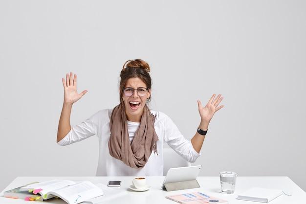 怒っている女性の上司は迷惑でジェスチャーし、否定的に叫ぶ