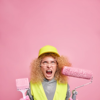 Angry female builder screams angrily focused above keeps mouth wide opened hods roller and brush being tired of repairing dressed in uniform