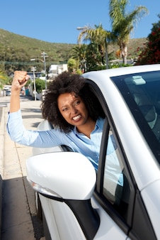Angry female car driver showing her fist while driving
