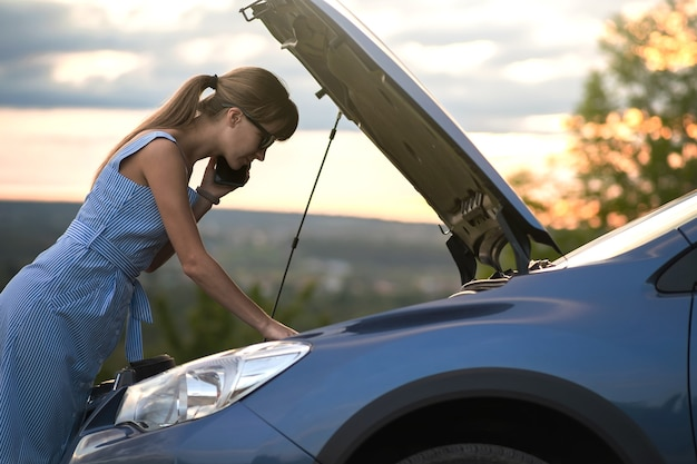 Angry female driver speaking angrily on cell phone with assistance service worker standing near a broken car with popped up hood while inspecting engine having trouble with her vehicle.