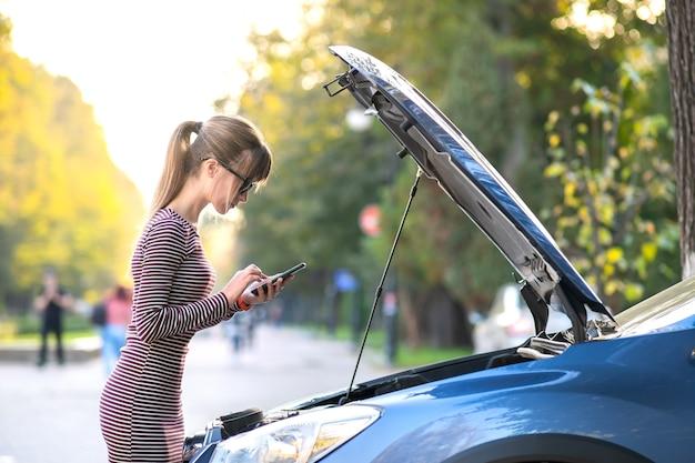 Злая женщина-водитель разговаривает по мобильному телефону с работником службы помощи, стоящим возле разбитой машины с поднятым капотом на обочине дороги, у которой проблемы с ее автомобилем.