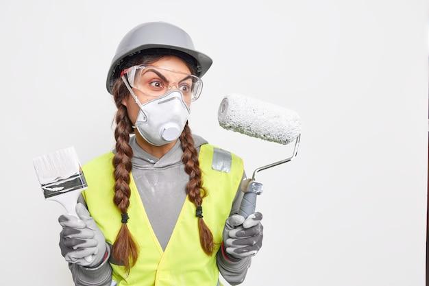 두 개의 땋은 머리를 가진 화난 여성 마스터는 집 재장식을 하느라 바쁜 그림 도구를 들고 있다