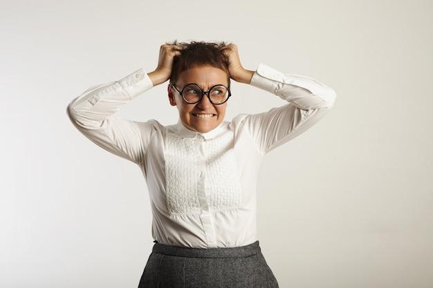 歯を食いしばって白い壁に彼女の髪の手でパニックに怒っている女教師