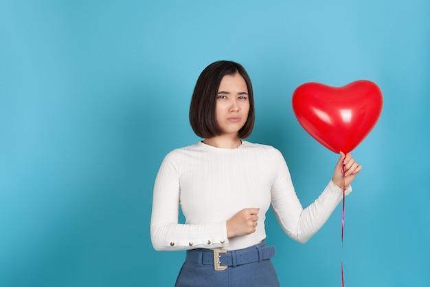 Злая свирепая молодая азиатская женщина держит летающий воздушный шар в форме сердца и сжимает руку в кулак