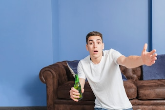 Angry football fan in front of couch