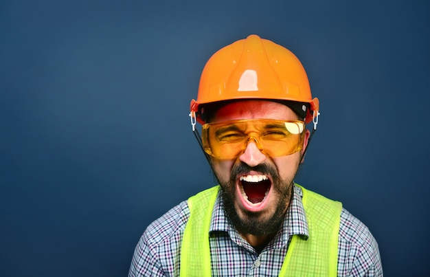 Angry foreman builder in hardhat shouting at workers