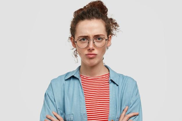 白い壁に向かってポーズをとって眼鏡をかけて怒っているそばかすのティーンエイジャー