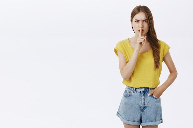 Ragazza arrabbiata e accigliata che zittisce, dice di stare zitta, zitta per favore