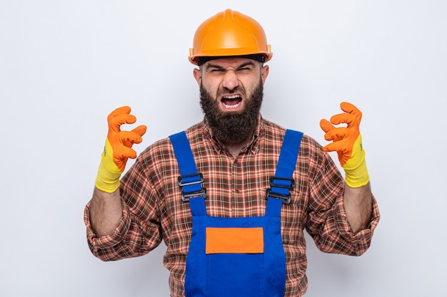 Uomo barbuto arrabbiato e frustrato del costruttore in uniforme da costruzione e casco di sicurezza che indossa guanti di gomma che grida e urla con espressione aggressiva alzando le braccia che si scatenano