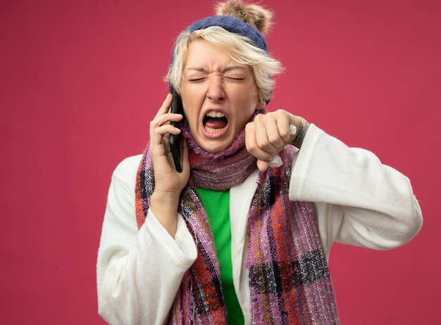 ピンクの壁の上に立っている携帯電話で話している間、暖かいスカーフと帽子の短い髪の怒っている欲求不満の病気の不健康な女性が気分が悪く叫んでいます