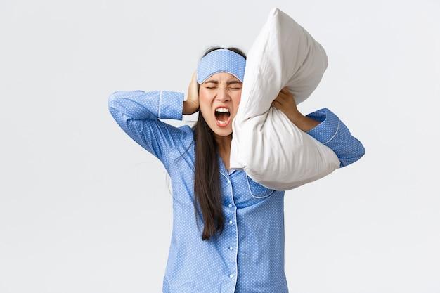 Злая разъяренная азиатская девушка в пижаме и спящей маске, лежа в постели и зажмурившись подушкой ушей, кричит безумно, как не может спать от громкого шума, соседи по вечеринке ночью, жалуясь на раздражающий звук.