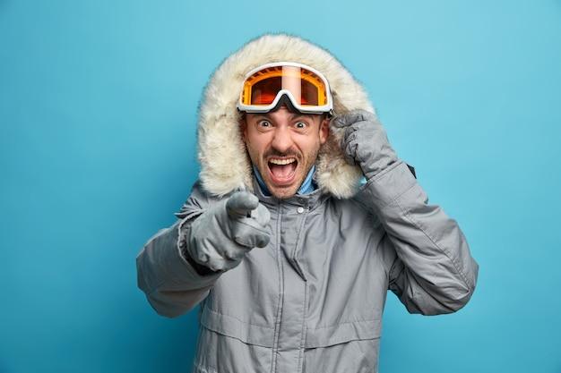 怒った猛烈な男はスキーウェアを着て怒って悲鳴を上げ、憤慨した表情のポイントは否定的な感情を表現し、山で冬休みを過ごしてスケートボードに行きます。レクリエーションの概念