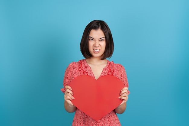 Angry furious young asian woman in red dress holding a large red paper heart and baring her teeth