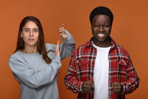 Злой разъяренный молодой темнокожий мужчина-обидчик, качающий кулаки и стиснув зубы, подавляющий ярость, готовый атаковать свою смущенную, напуганную жену. ссора, ссора и проблемы в отношениях