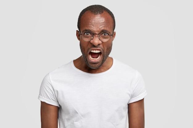 怒っている猛烈な青年が叫び、白い壁に隔離された誰かと議論している間、悲惨な気分になります