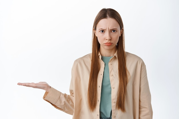 Angry girl frowning, holding in open hand over copyspace, showing item on palm against copyspace, looking with anger and displeased face, standing over white background.
