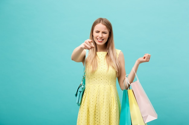 파란색 배경에 고립 된 드레스에 화난 소녀. 테이크 아웃을 위한 쇼핑 종이 봉지를 들고 손가락을 가리킵니다.