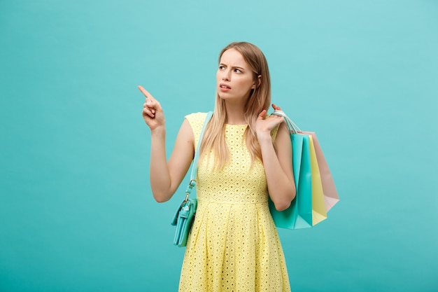 青い背景に分離されたドレスの怒っている女の子。持ち帰り用の買い物用紙袋を持って指を指す。