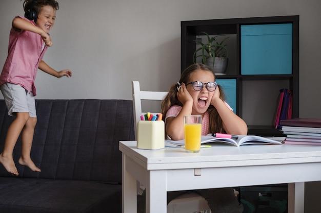 남동생이 방해하는 동안 집에서 공부하는 안경을 쓴 화난 소녀.