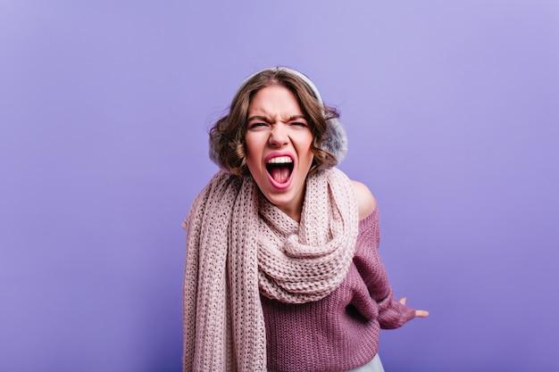 Сердитая девушка в меховых серых наушниках кричит. внутреннее фото эмоционально удивленной дамы в шарфе, изолированном на фиолетовой стене.