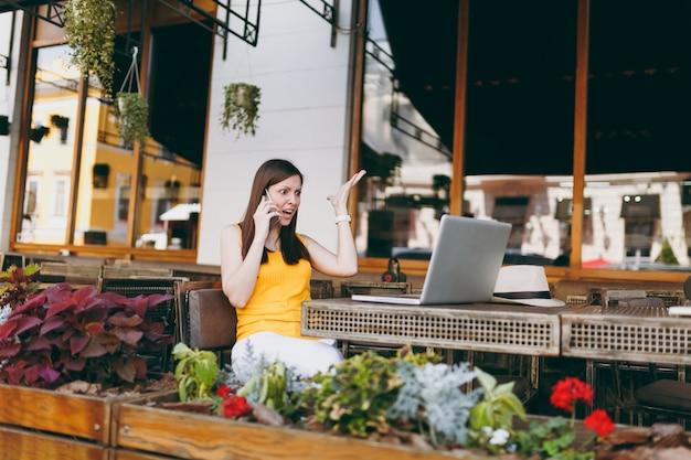 야외 거리 카페에서 노트북 pc 컴퓨터와 함께 테이블에 앉아 휴대 전화로 이야기하고, 비명을 지르고, 자유 시간 동안 레스토랑에서 문제를 방해하는 화난 소녀