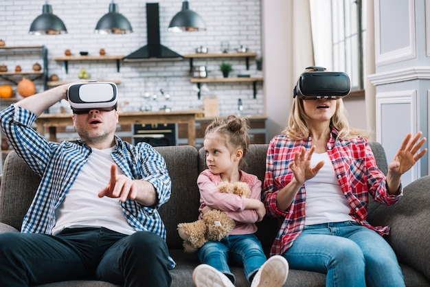 Angry girl looking her father while wearing virtual reality glasses sitting on sofa