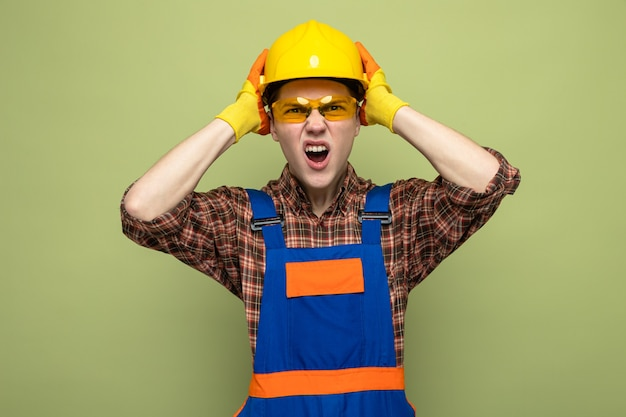 Angry grabbed head young male builder wearing uniform and gloves with glasses