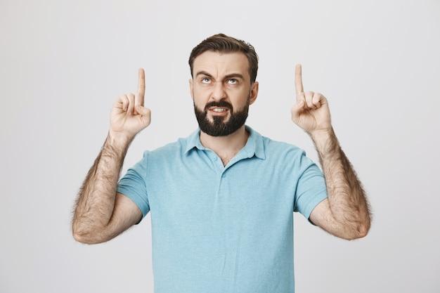 Uomo arrabbiato che fa smorfie che punta le dita verso l'alto e sembra pazzo