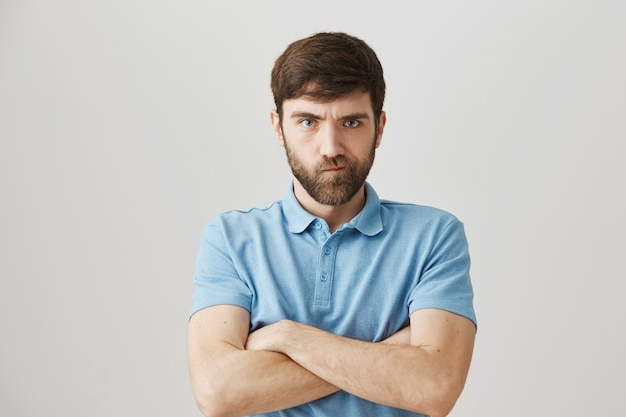 Angry grumpy young bearded man posing