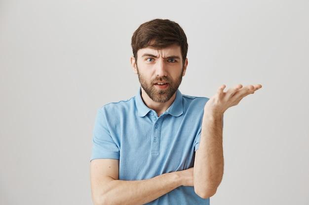 Angry grumpy young bearded man posing
