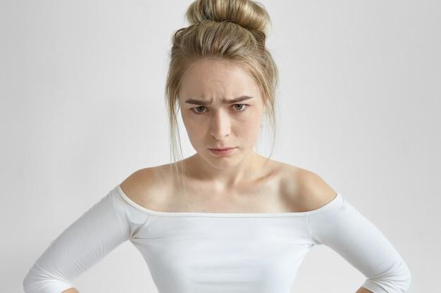 Giovane femmina europea scontrosa arrabbiata con l'acconciatura disordinata accigliata, arrabbiata con il marito irresponsabile. donna irritata in top alla moda che esprime emozioni negative e fastidio